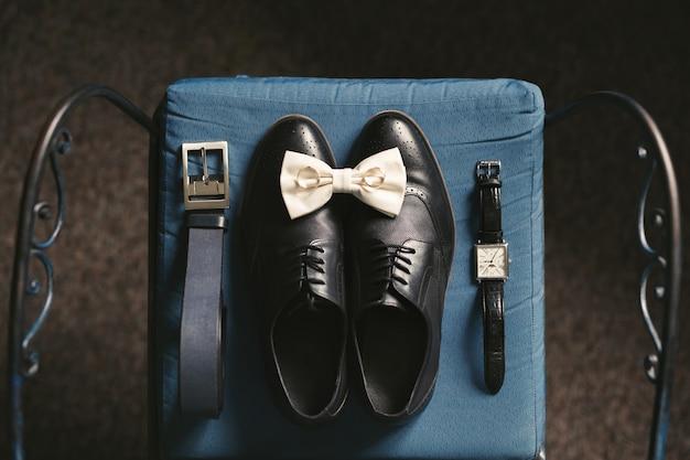 Sapatos masculinos, relógio e anéis na cadeira