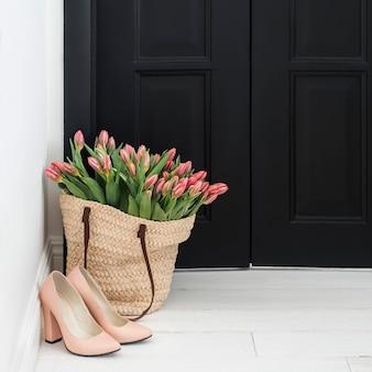 Sapatos nus e saco de palha com monte de tulipas rosa frescas no chão perto da porta preta