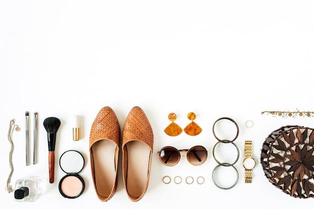 Sapatos, óculos de sol, bolsa de mão, relógio, pó, batom, escova, anéis, pulseira, perfume.