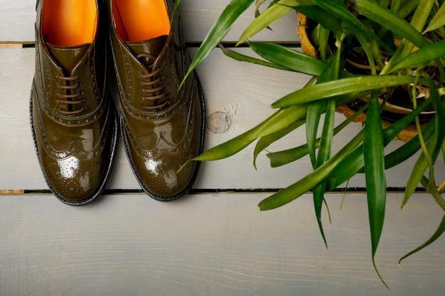 Sapatos oxford lacado verde sobre fundo de madeira