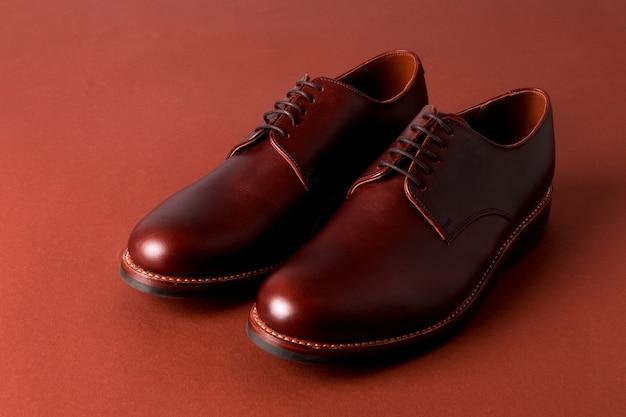 Sapatos oxford marrons na superfície vermelha