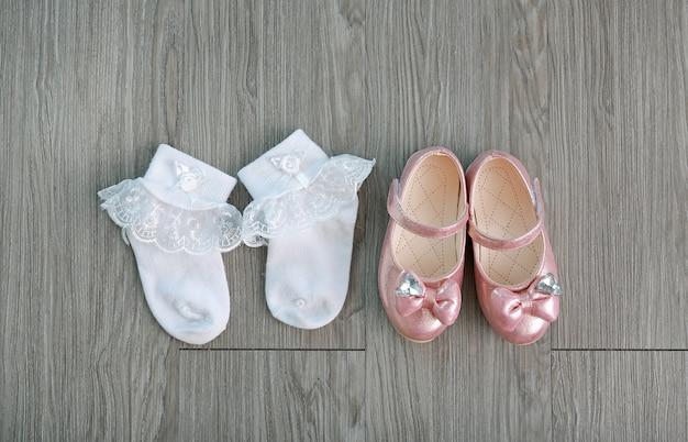 Sapatos pequenos da menina com meias brancas na madeira