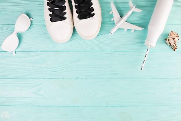 Sapatos pintados de branco com avião de brinquedo e garrafa com palha