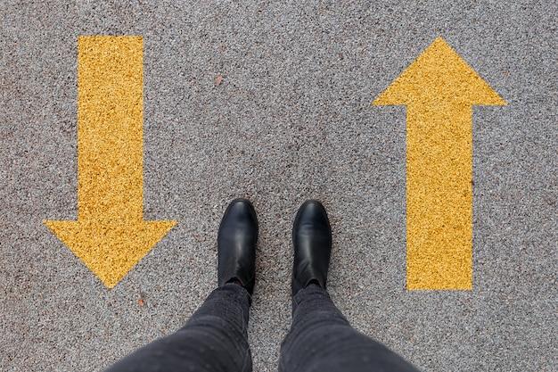 Sapatos pretos em pé no chão de concreto asfáltico com duas setas amarelas.