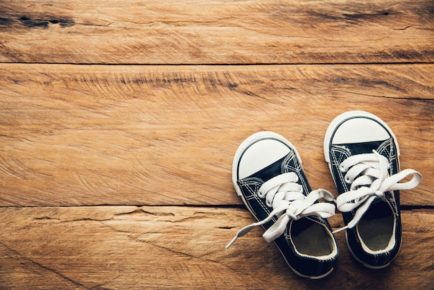 Sapatos pretos para crianças no chão de madeira