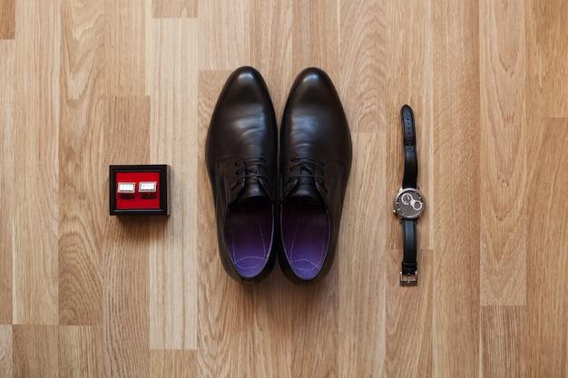 Sapatos pretos, relógio e abotoaduras no chão. acessórios para o noivo no dia do casamento.