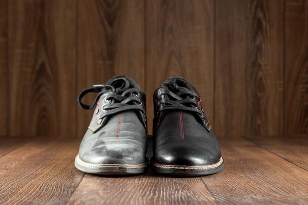 Sapatos pretos, um segundo limpo e sujo em uma parede de madeira. o conceito de engraxate, cuidados com a roupa, serviços.