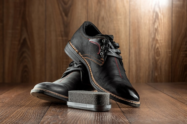Sapatos pretos um segundo limpo sujo e escova em uma parede de madeira. o conceito de engraxate, cuidados com a roupa, serviços.
