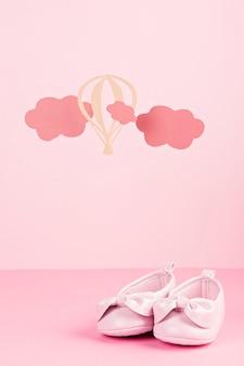 Sapatos rosa bebê fofo sobre o fundo rosa pastel com nuvens e balões