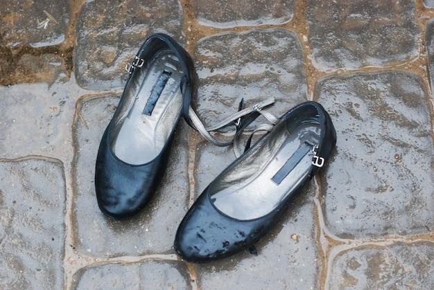 Sapatos velhos estão na rua na chuva, sapatos molhados
