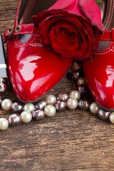 Sapatos vermelhos com flor rosa e joias de pérolas em madeira