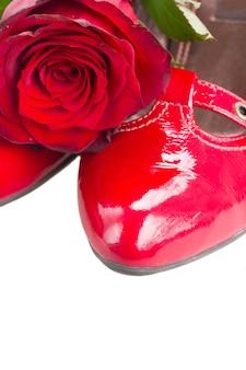 Sapatos vermelhos com flor rosa perto da borda isolada no fundo branco
