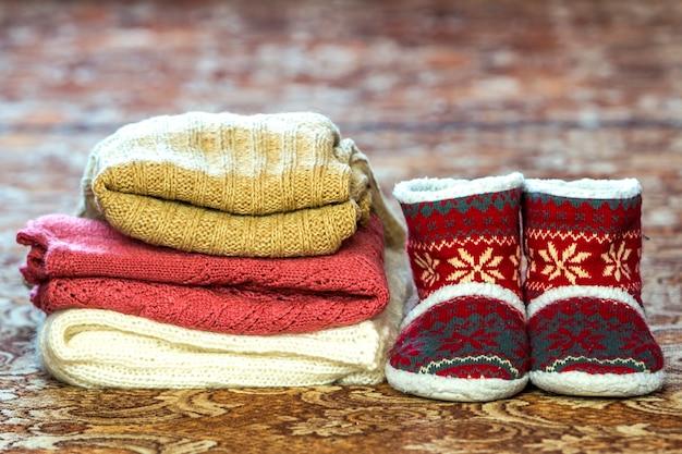 Sapatos vermelhos e uma pilha de blusas de malha