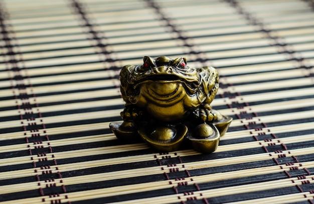 Sapo da sorte chinês em uma esteira de bambu