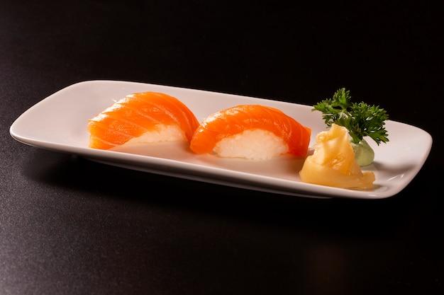 Saquê - nigiri sushi com salmão cru em fundo preto