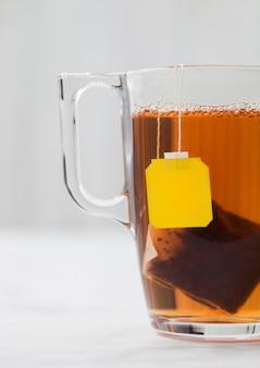 Saquinho de chá preto de etiqueta amarela em copo de vidro transparente sobre fundo branco.