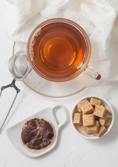 Saquinho de chá usado em placa de cerâmica com copo de chá e infusor de peneira e açúcar de cana em fundo branco.