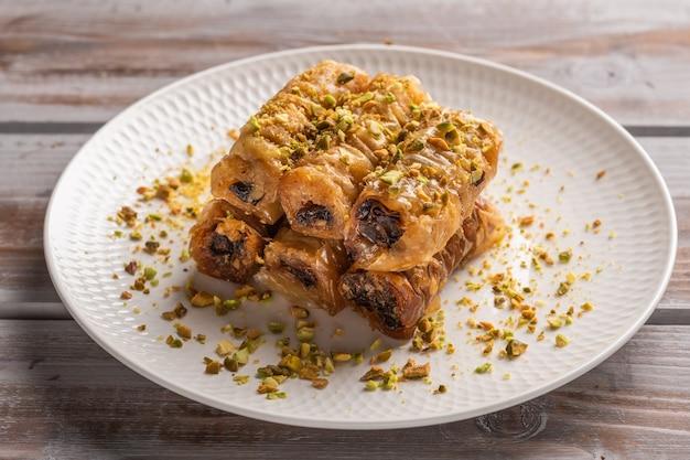 Saragli de pastelaria tradicional grega em um prato branco com pistache em uma superfície de madeira close-up