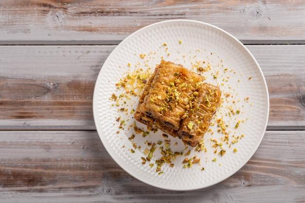 Saragli de pastelaria tradicional grega em um prato branco em uma vista superior de superfície de madeira