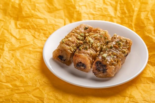 Saragli de pastelaria tradicional grega em um prato branco sobre uma superfície de papel amarelo