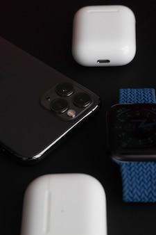 Saratov, rússia - 10 de junho de 2021: computador macbook, iphone, airpods e relógio na mesa preta, criado pela apple inc.