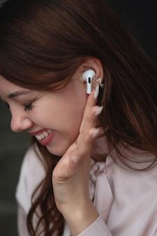 Saratov, rússia - 15 de junho de 2021: retrato de uma jovem elegante e alegre. uma linda jovem com fones de ouvido sem fio, airpods ouve música e música com bom humor