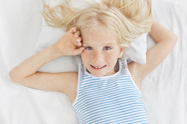 Sardenta garota de olhos azuis com cabelo loiro, vestindo camiseta listrada, olhando com expressão deliciosa enquanto estava deitado na roupa de cama branca. criança do sexo feminino muito pequena, aproveitando o bom dia na cama.