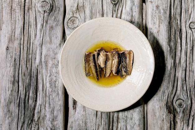 Sardinhas defumadas em óleo servidas em prato de cerâmica branca sobre superfície de madeira cinza velha. vista superior, configuração plana. copie o espaço