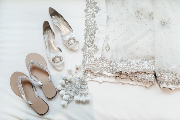 Sarees de luxo e sapatos de noiva indiana em fundo branco
