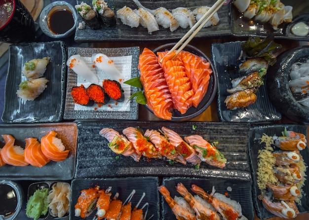 Sashimi de salmão e outros frutos do mar e sushi na mesa da festa