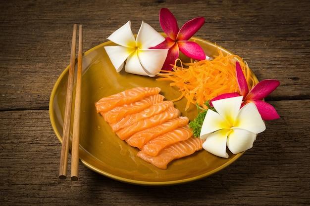 Sashimi de salmão no prato com flor em madeira velha