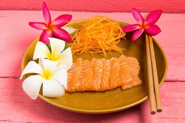Sashimi de salmão no prato com flor na cor rosa de madeira