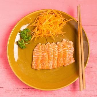 Sashimi de salmão no prato na cor rosa de madeira