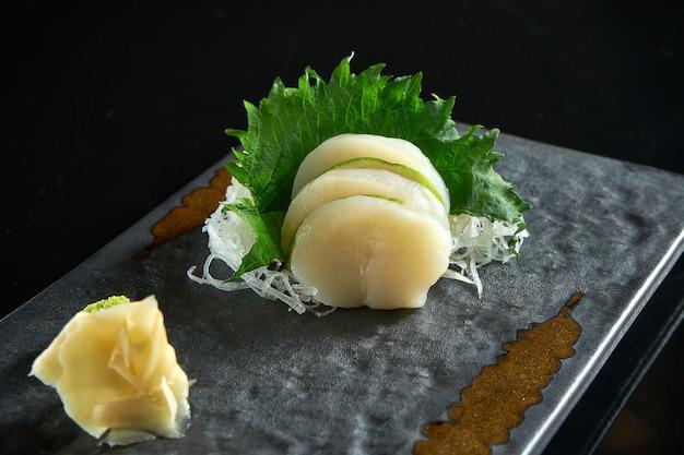 Sashimi fresco de vieiras fatiadas com rabanete servido em uma placa preta sobre uma mesa preta. comida japonesa