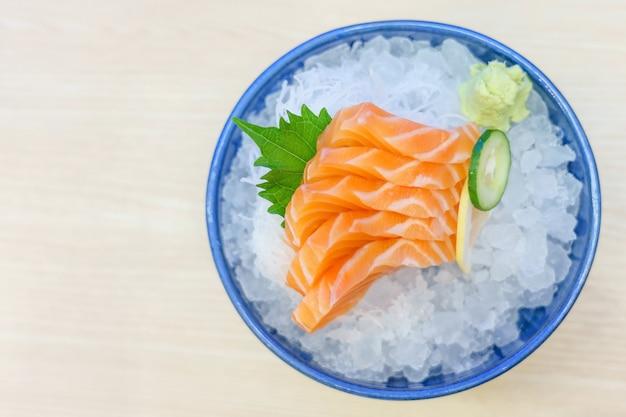 Sashimi salmon no saque do gelo com a corrediça fresca do wasabi e da cenoura, estilo japonês do alimento.