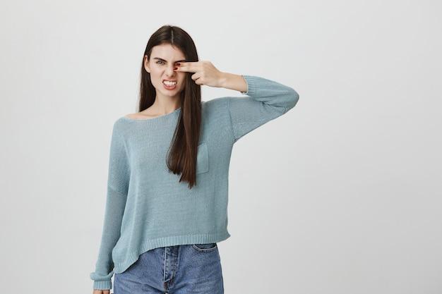 Sassy mulher capa olho com palma mostrando os dentes