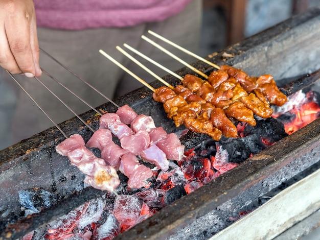 Satay de alimentos indonésio queimado usando carvão