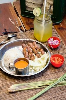 Satay de comida indonésia servido com molho de amendoim e rolo de bolo de arroz