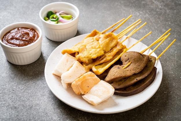 Satay de porco e satay de fígado com molho de pão e amendoim e picles que são rodelas de pepino e cebola em vinagre - estilo de comida asiática