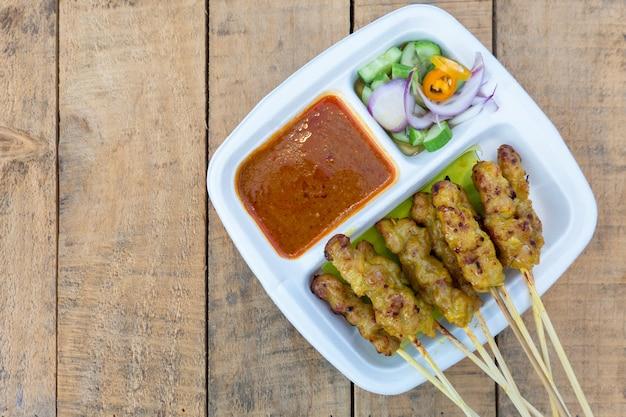 Satay de porco grelhado de porco servido com molho de amendoim ou molho agridoce, comida tailandesa