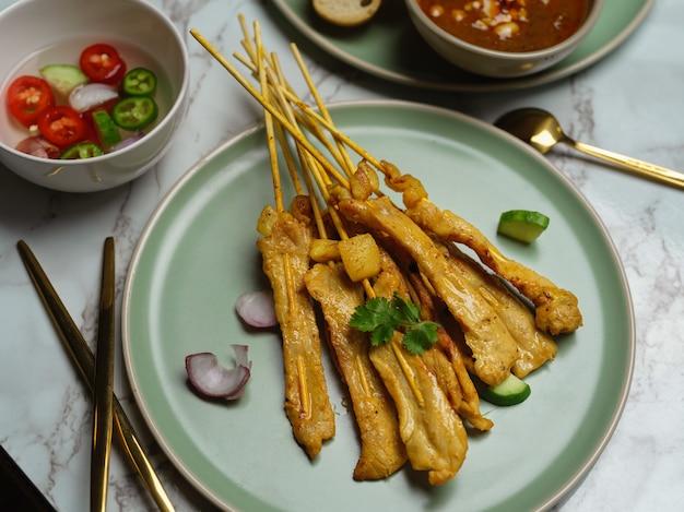Satay de porco grelhado (moo satay) com pepino e cebola servido com molho de amendoim e acompanhamento