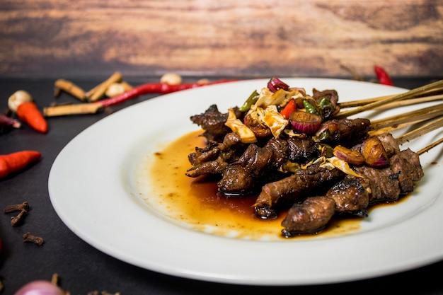 Satay é um alimento feito de carne cortada em pequenos pedaços e espetada