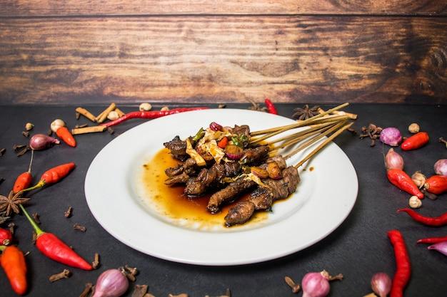 Satay prato de frango em um prato branco