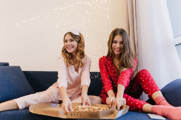 Satisfeita a garota encaracolada de pijama rosa, sentada no sofá azul e desfrutando de fast food. senhora de cabelos compridos em traje de noite vermelho comendo pizza com a amiga.