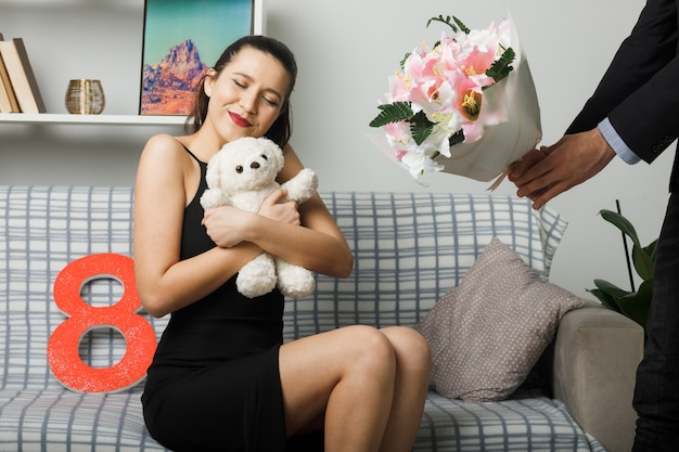 Satisfeita com os olhos fechados, jovem feliz no dia da mulher, sentada no sofá segurando o ursinho de pelúcia na sala de estar