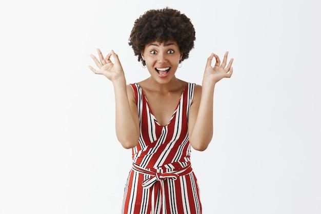 Satisfeita e animada, atraente mulher de pele escura, de macacão listrado vermelho, mostrando gestos de ok ou ok perto do rosto e sorrindo alegremente