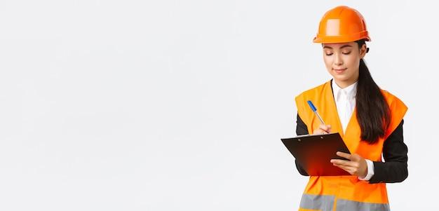 Satisfeita, engenheira de construção asiática, arquiteta fazendo anotações na prancheta, escrevendo algo durante a inspeção na área de construção, usando capacete de segurança, empresária inspecionar trabalhadores