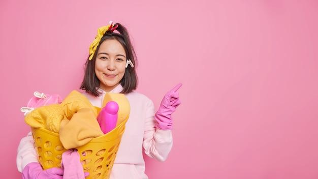 Satisfeita governanta mulher asiática com cabelo escuro usa moletom e luvas protetoras de borracha mantém o cesto de roupa suja indica de lado no espaço em branco isolado sobre fundo rosa. conceito de limpeza