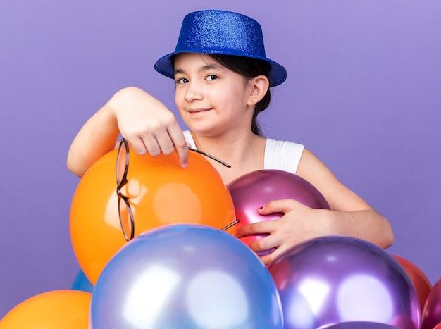 Satisfeita jovem caucasiana com chapéu de festa azul segurando óculos ópticos em pé com balões de hélio isolados na parede roxa com espaço de cópia