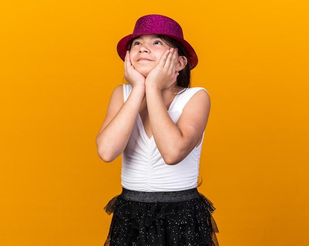 Satisfeita jovem caucasiana com chapéu de festa roxo, colocando as mãos no rosto e olhando para cima, isolada na parede laranja com espaço de cópia